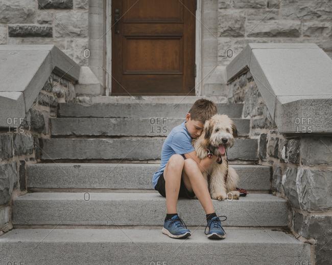 Boy embracing dog while sitting on steps