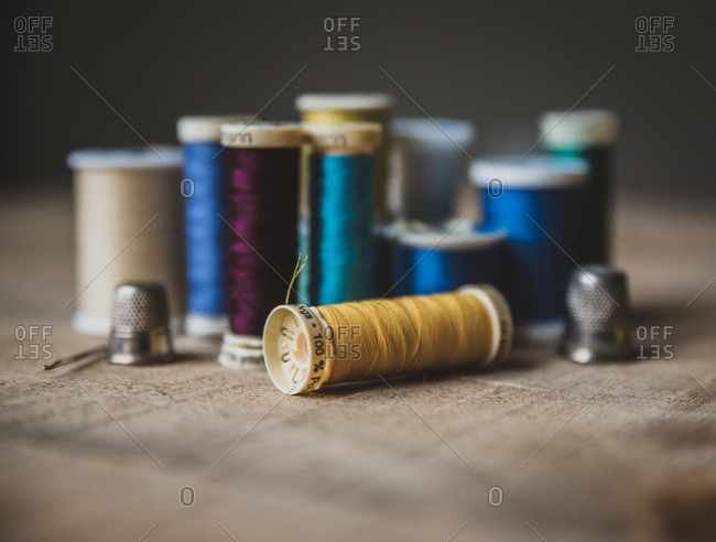 Close-up of colorful spools with thimbles on wooden table at workshop