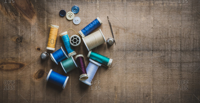 High angle view of colorful spools with thimbles and buttons on wooden table at workshop