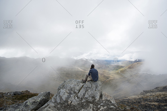 Rear view of man sitting on cliff against landscape during foggy weather