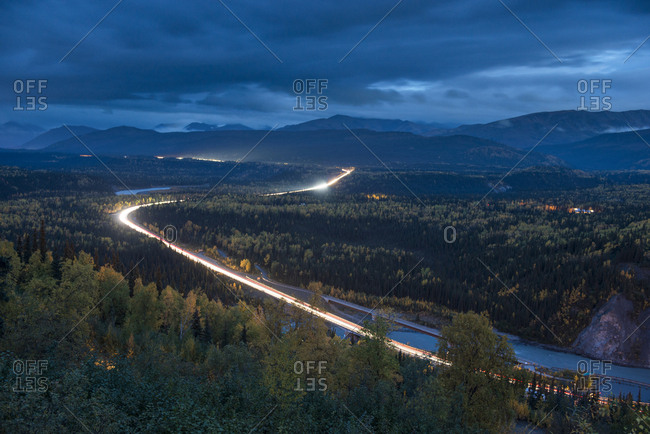 Long exposure of vehicles on road against sky at night