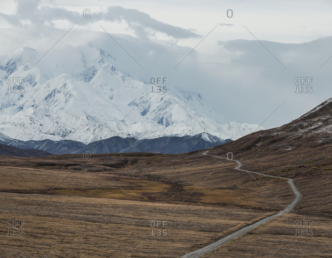 High angle view of road amidst field against snowcapped mountains at Denali National Park and Preserve during foggy weather