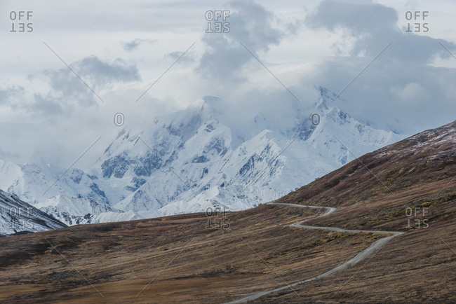 Scenic view of road amidst field against snowcapped mountains at Denali National Park and Preserve during foggy weather