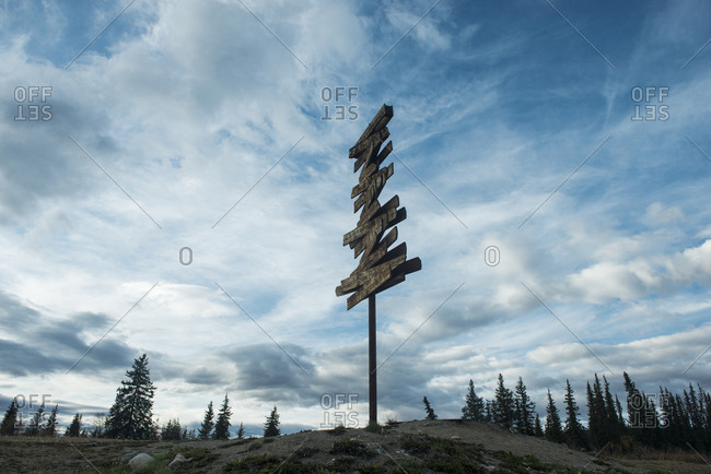 Signboard on field against sky