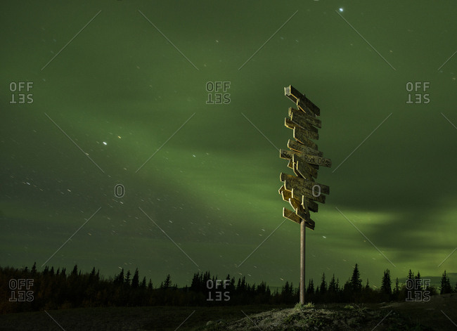 Signboard on field against aurora borealis at night
