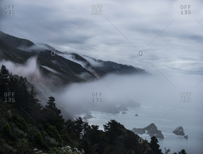 High angle idyllic view of mountains by sea against cloudy sky during foggy weather