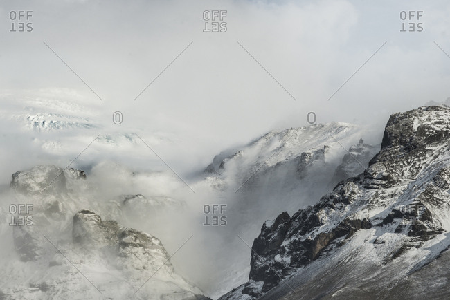 High angle view of snowcapped mountains against cloudy sky during foggy weather