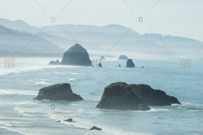 High angle idyllic view of rock formations in sea against mountains