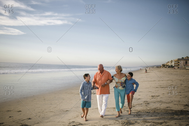 Happy grandparents with grandsons walking at beach against sky