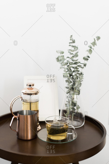 Drinks with picture frame and houseplant on table against white wall