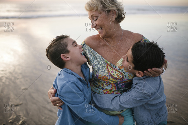 Happy grandmother with grandsons standing at beach during sunset