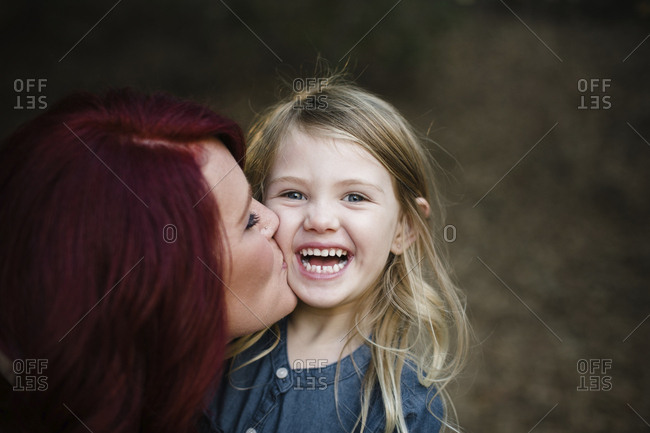Portrait of cheerful daughter with mother kissing her
