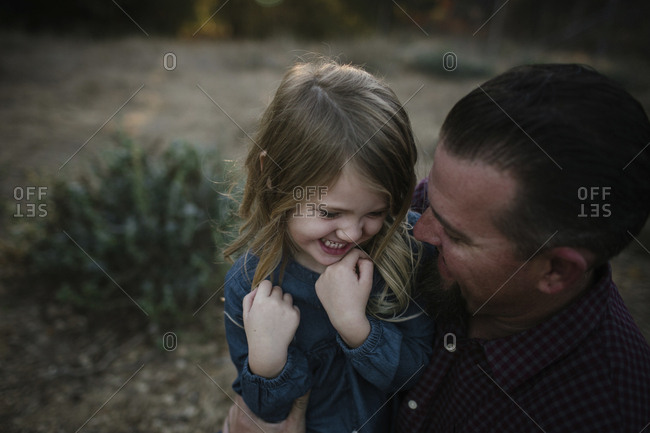 Cheerful father and daughter on field