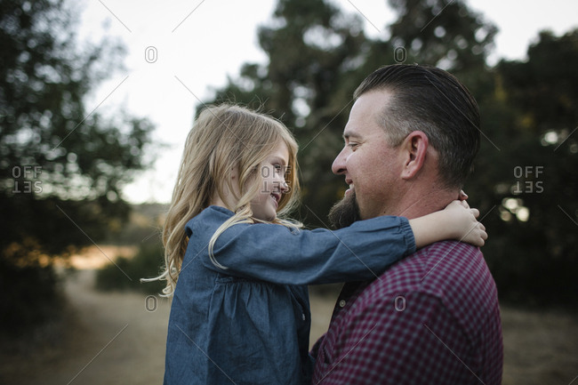 Side view of father and daughter looking at each other on field