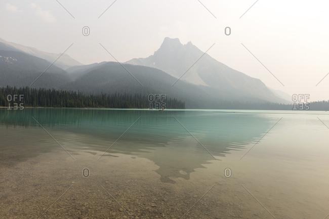 Scenic view of lake by mountains at Yoho National Park against sky during foggy weather