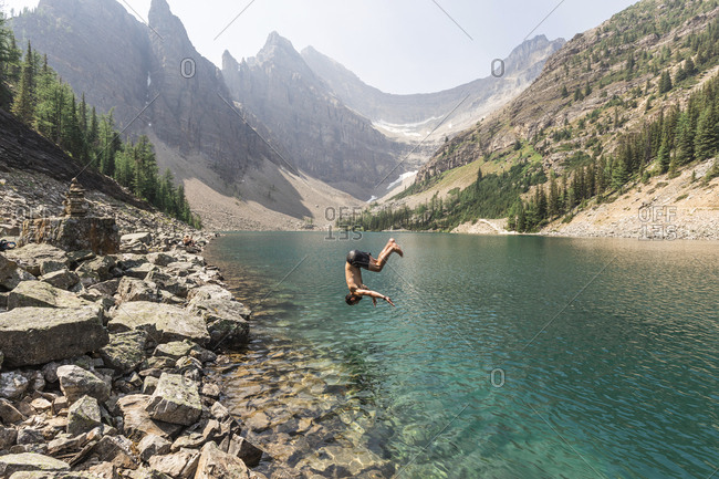 Side view of man diving in lake against mountains at Banff National Park