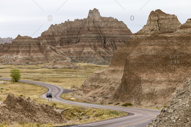 Vehicle on road amidst mountains at Badlands National Park