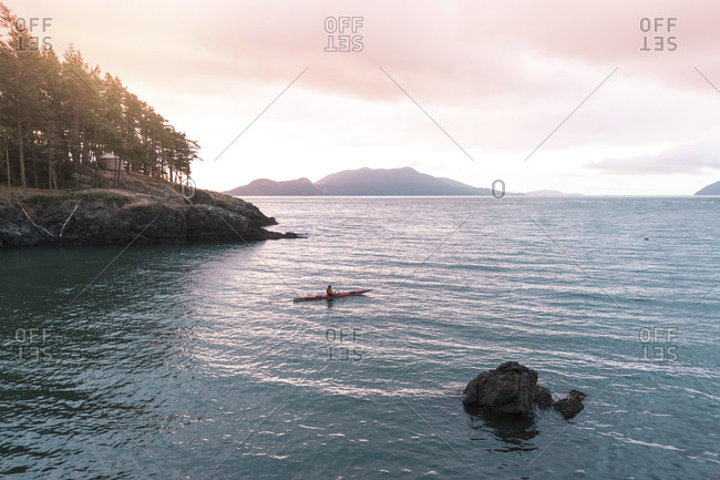 Mid distance view of woman kayaking on river against sky