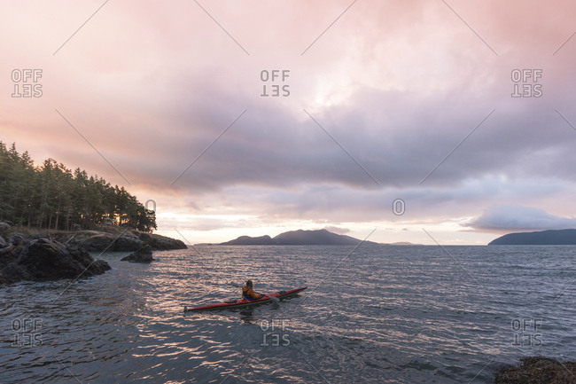 Woman kayaking on river against cloudy sky during sunset