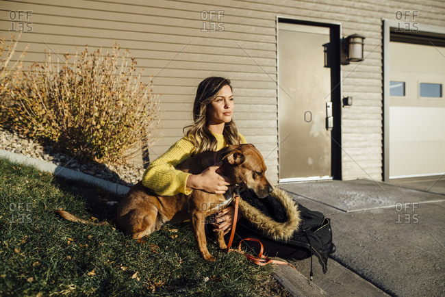 Woman with dog looking away while sitting at yard during sunny day