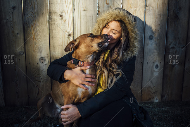 Woman with dog sitting against wooden fence
