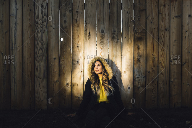Woman in winter coat sitting against wooden fence