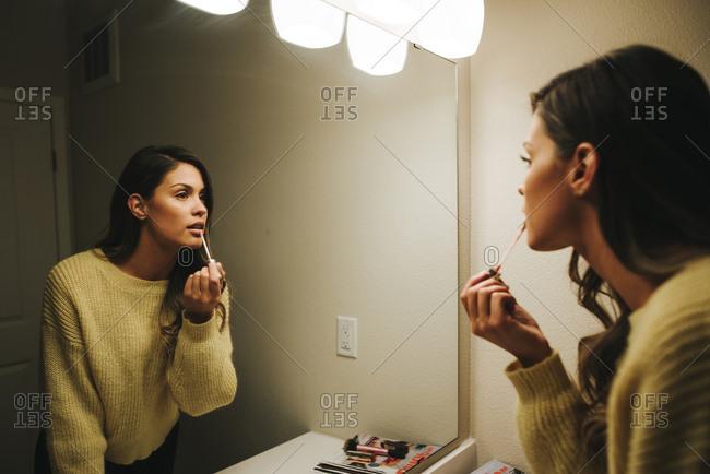 Woman applying lip gloss reflecting on mirror at home
