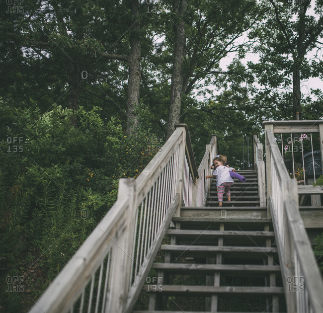Low angle view of playful siblings climbing wooden steps
