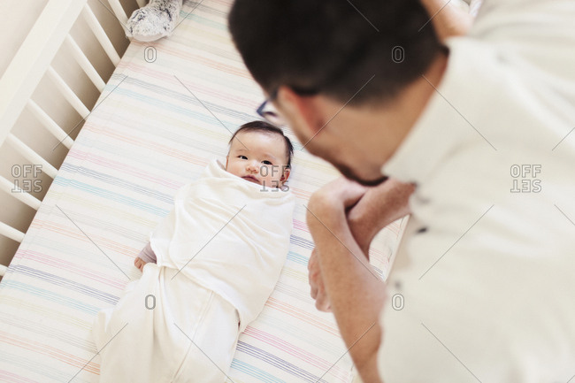 High angle view of father looking at newborn daughter lying in crib at home