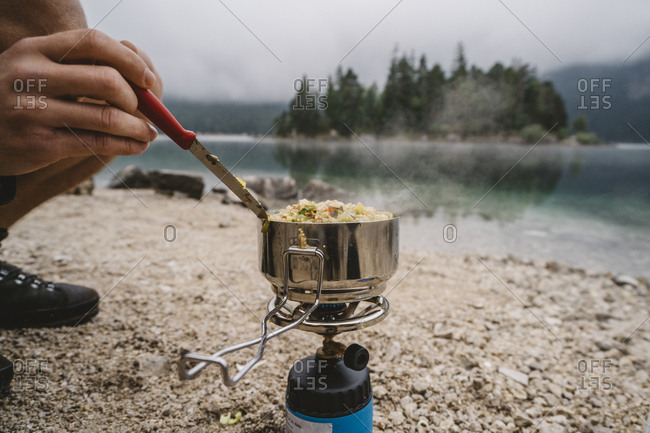Low section of man preparing food on camping stove while crouching at lakeshore in forest
