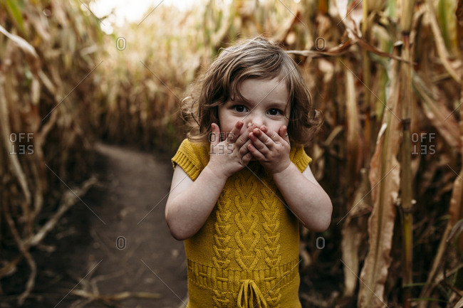 Portrait of girl with hands covering mouth standing in farm
