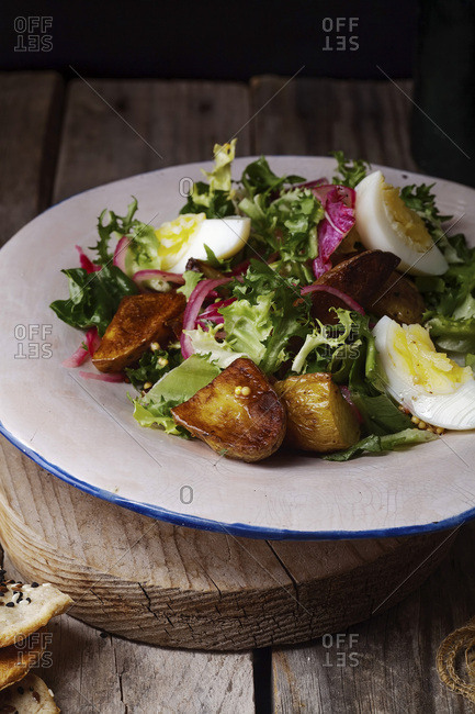 Potato salad with marinated onion, eggs and grain mustard. Old wooden background.