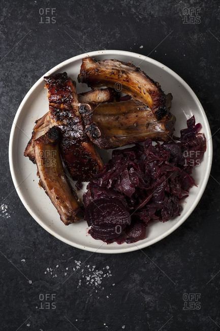 Grilled pork ribs cooked with balsamic vinegar and honey sauce, garnished with red wine braised red cabbage with beets on white plate. Dark rustic background.
