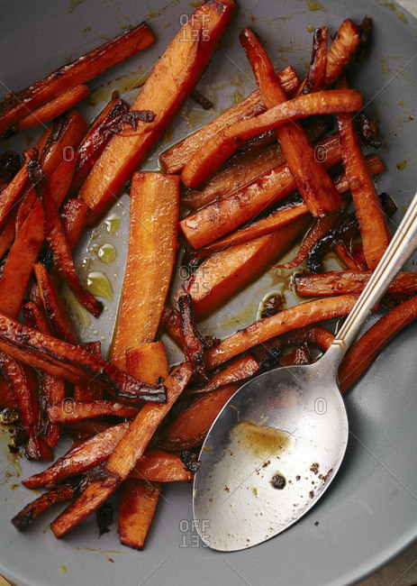 Close up shot of roasted caramelized carrots with olive oil and honey sauce in gray bowl.