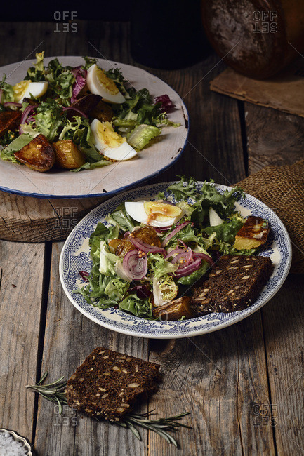 Potato salad with eggs, marinated onion, and grain mustard dressing served in two vintage plates. Old wooden background