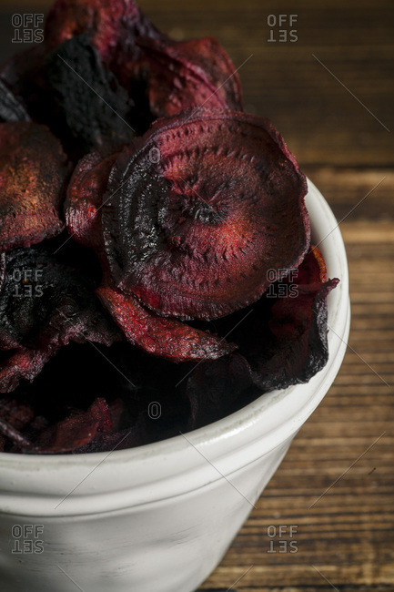 Organic homemade beetroot chips cooked in oven with olive oil, pepper and salt in white ceramic bowl on wooden background. Vertical composition, close-up view