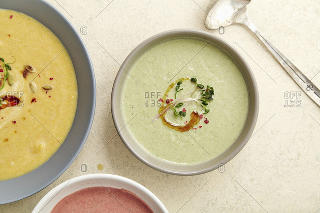 Flatlay with three bowls with colorful vegetarian creamy soups with broccoli, pumpkin and beetroot garnished with pumpkin seeds and olive oil on beige textured background