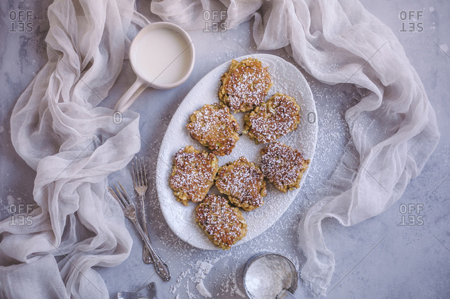 Sweet apple fritters sprinkled with powdered sugar on a white serving plate