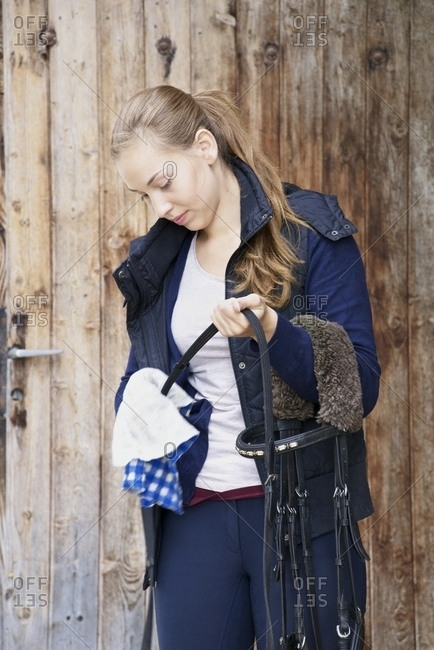 Young Woman Cleaning Tack, Baden-Wuerttemberg, Germany, Europe