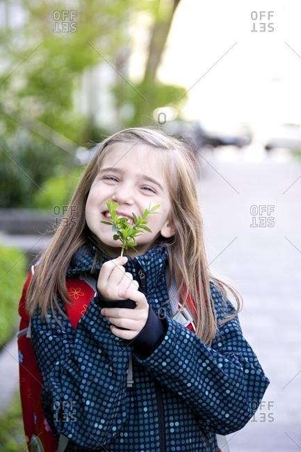 Little schoolgirl holding evergreen twig, Munich, Bavaria, Germany