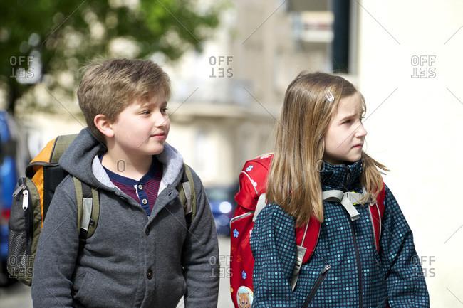 Two children walking to school, keeping an eye on the traffic, Munich, Bavaria, Germany