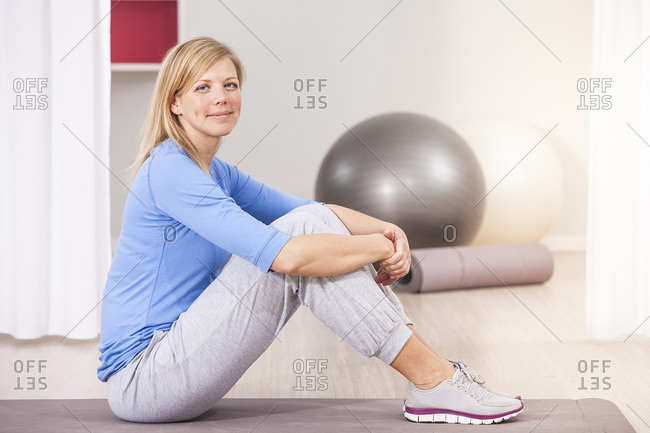 Woman with blond hair taking a break in gym