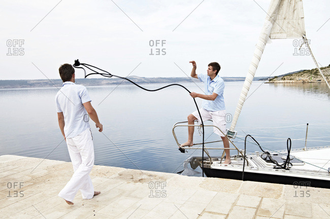Croatia, Sailboat entering port, Two young men fixing rope