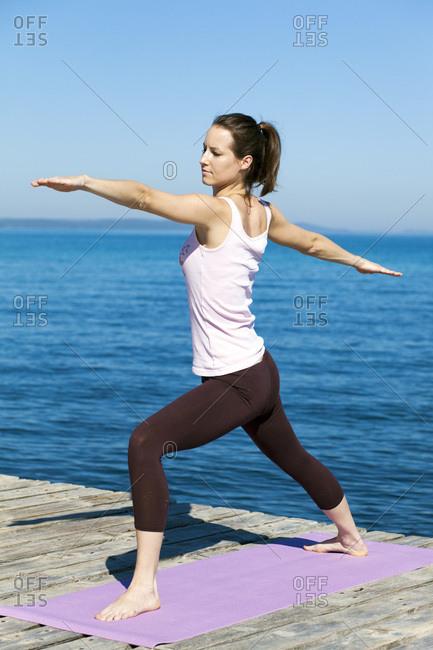 Woman practicing yoga on a boardwalk, warrior pose