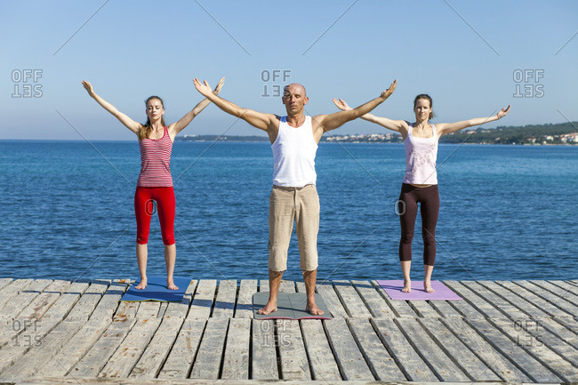 People practicing yoga on a boardwalk, arms outstretched