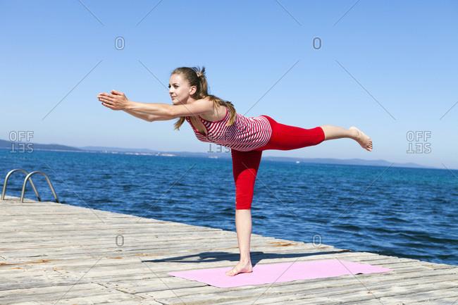 Woman practicing yoga on a boardwalk, warrior pose on one leg