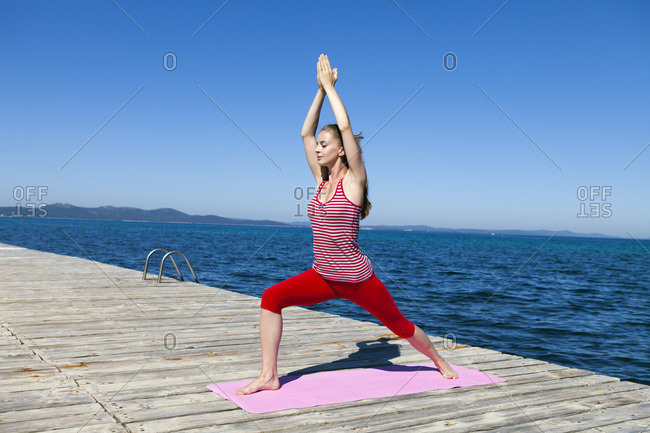 Woman practicing yoga on a boardwalk, arms raised