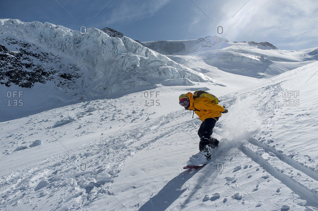 Man snowboarding in mountain scenery, European Alps, Tyrol, Austria