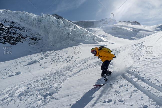 Man snowboarding in mountain scenery, European Alps, Tyrol, Austria