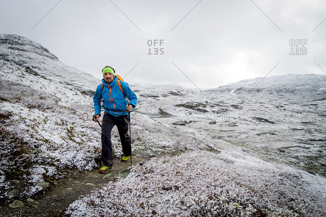 Man speed hiking along snowcapped trail, Norway, Europe